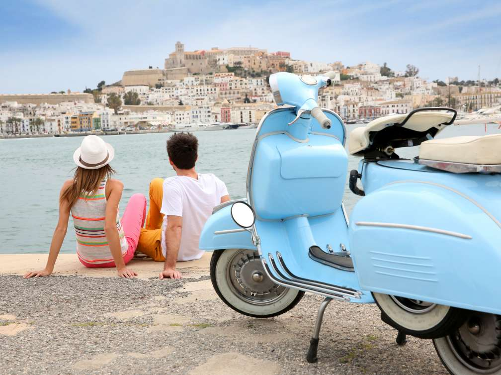 Tourists looking at the town of Ibiza, moto in foreground
